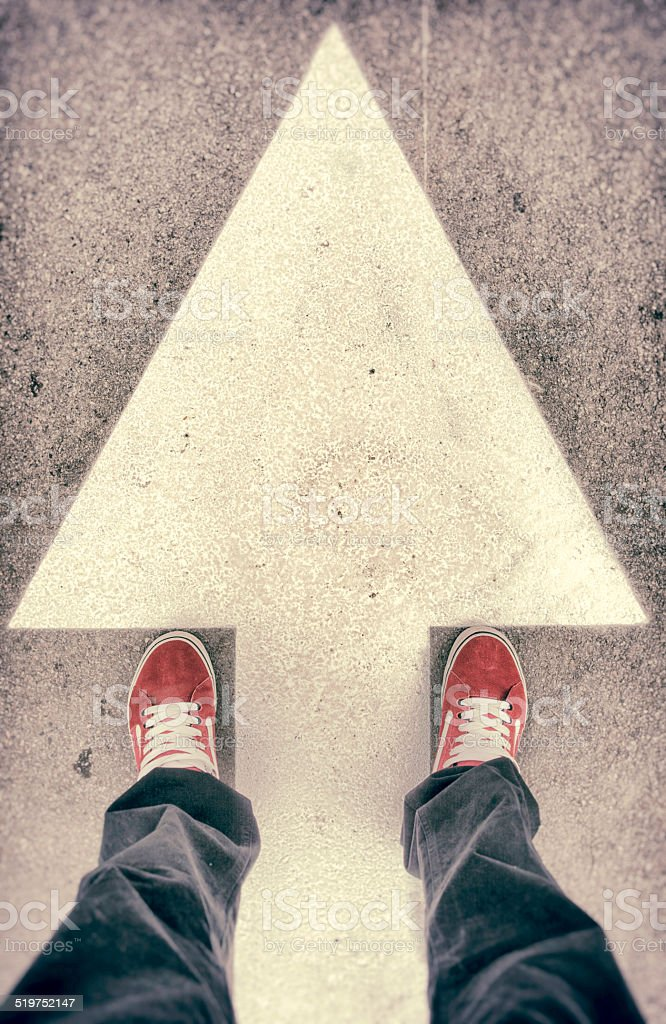 Shoes and forward arrow sign from above stock photo