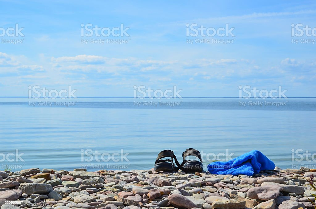 Shoes and towel at coast stock photo