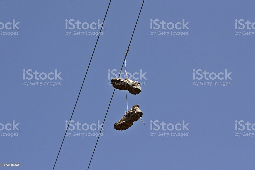 Shoes hang from a telephone wire stock photo