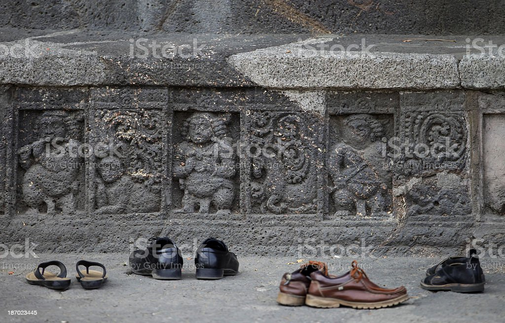 Shoes sit next to carvings near a temple stock photo