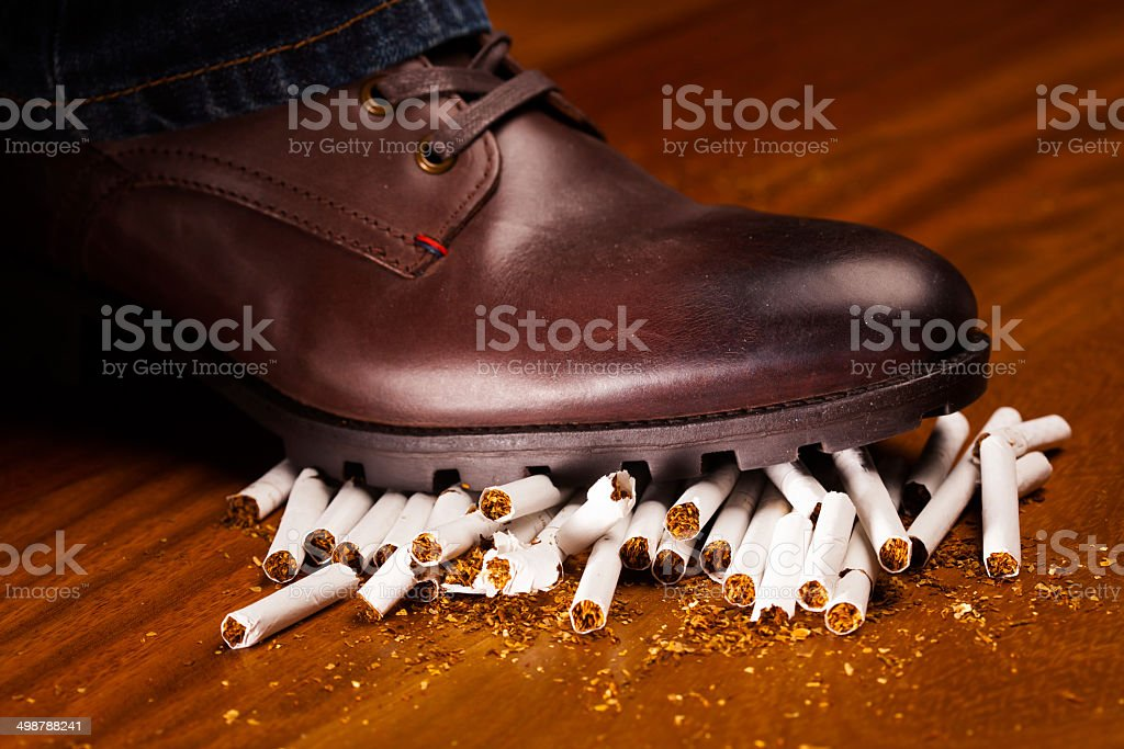 shoes trampling down on cigarettes stock photo