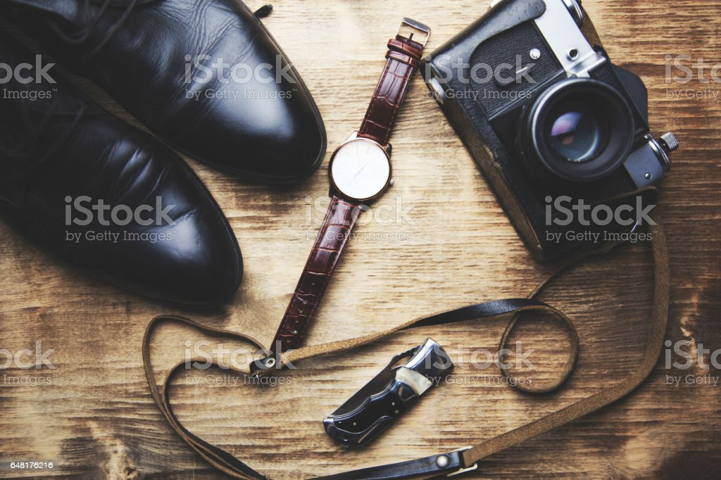 shoes watch, wallet and camera on wooden background stock photo
