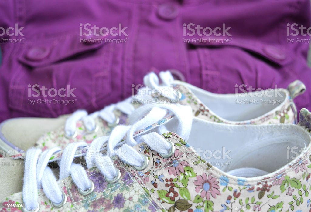 Shoes with flowers and purple jacket on background stock photo