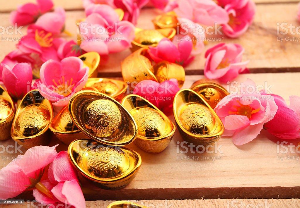 shoe-shaped gold ingot and Plum Flowers stock photo