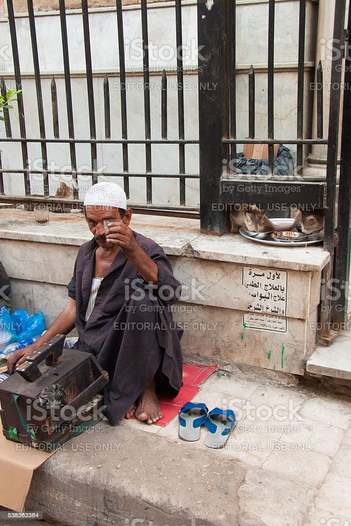 Shoeshiner and cats in the background in a Cairo street stock photo