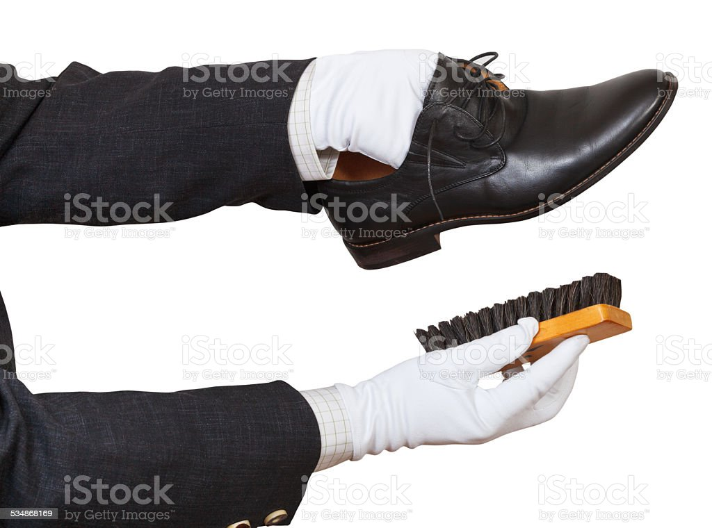 Shoeshiner in white gloves cleaning black shoes stock photo