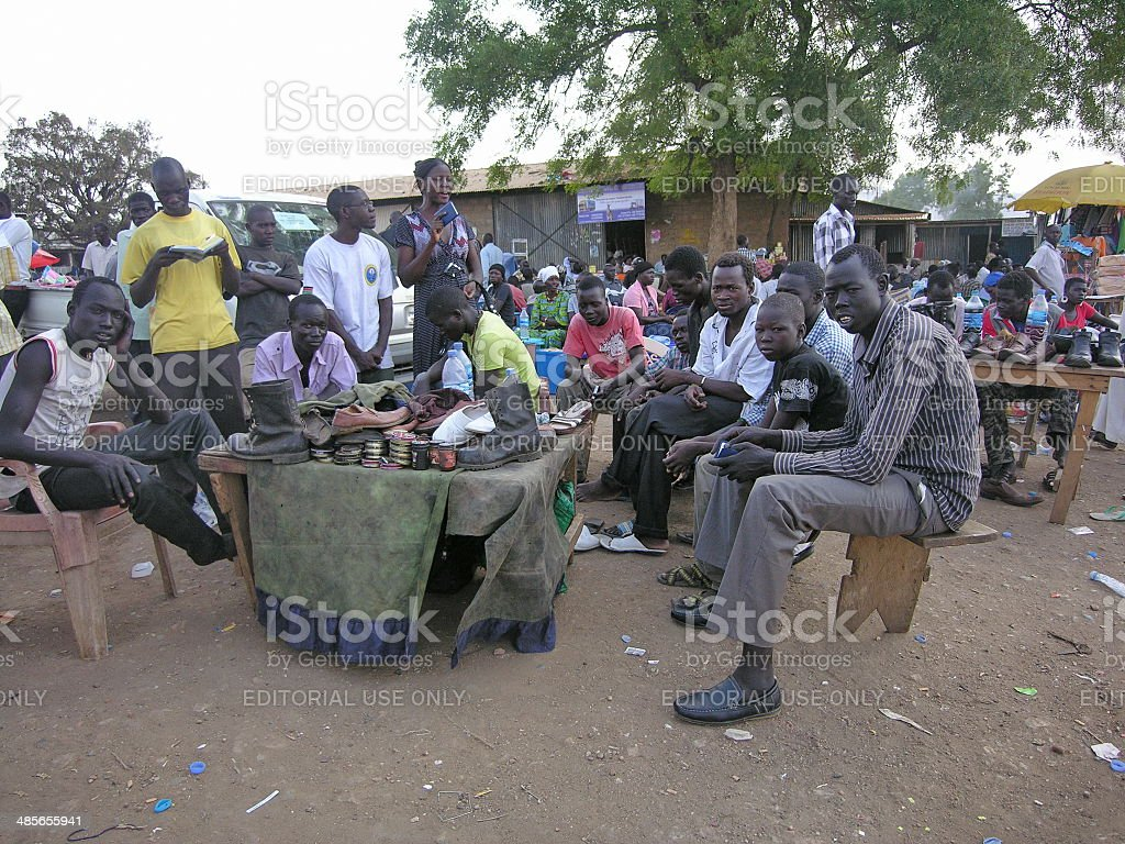 Shoeshiners wait for clients at Juba's market, South Sudan. royalty-free stock photo
