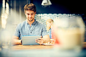 Shoot through of attractive man using digital tablet at cafe