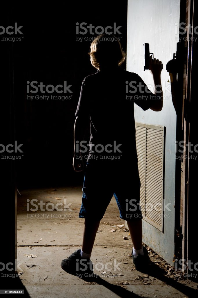 A silhouette of a person holding a handgun in a doorway....
