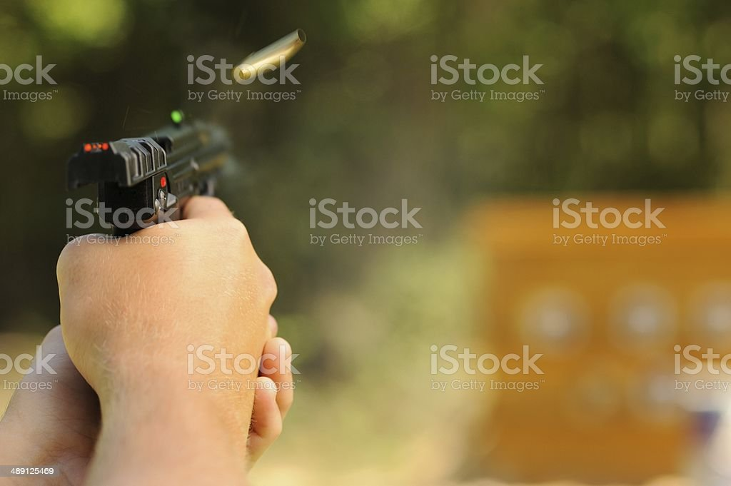 Shooting gun at targets with bullet ejecting stock photo