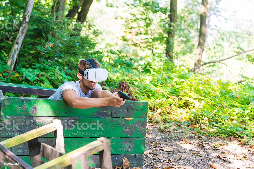 Shooting man in virtual reality headset playing video game stock photo