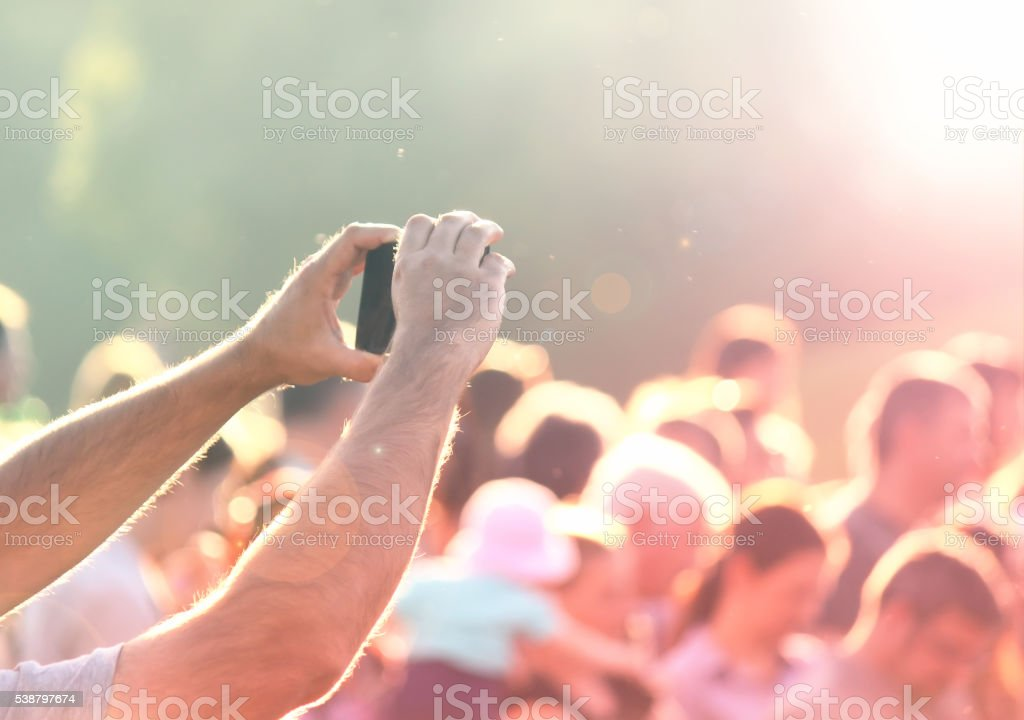 Shooting photos with a mobile phone in a crowd stock photo