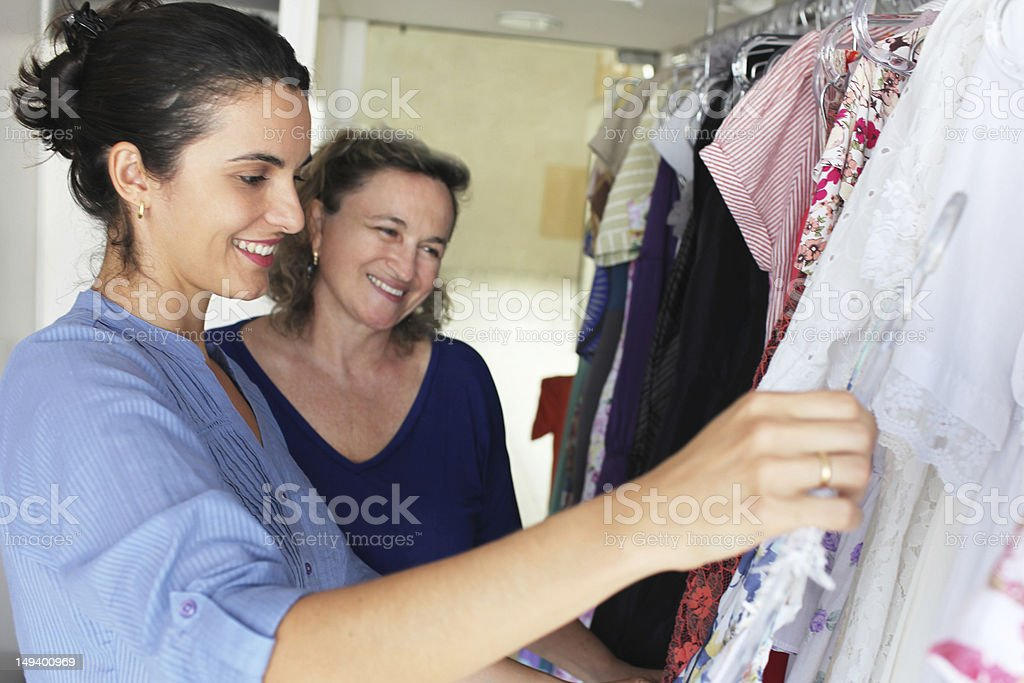 Shop assistant helps older woman choosing clothes royalty-free stock photo