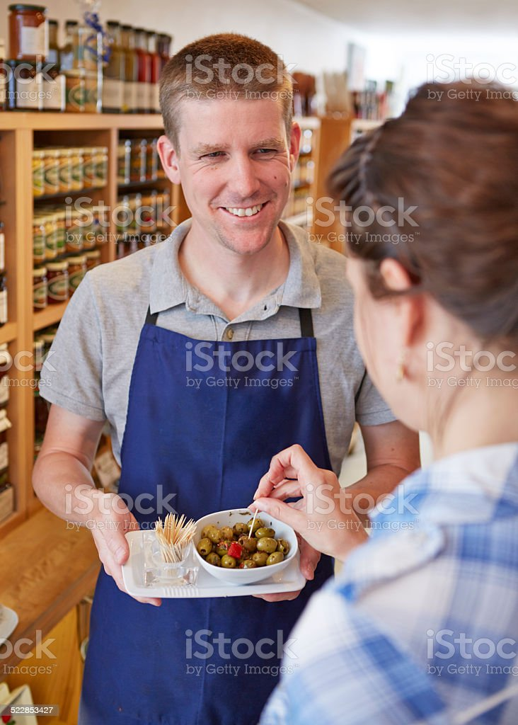 Shop assistant offering olive to customer in delicatessen stock photo
