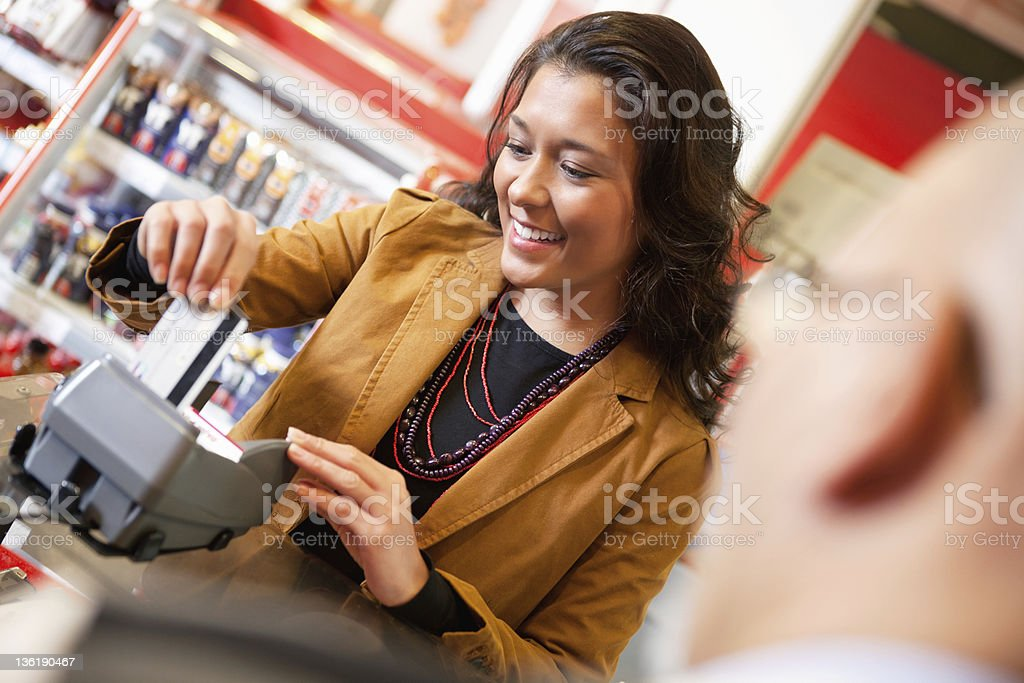 Shop assistant smiling while swiping credit card royalty-free stock photo