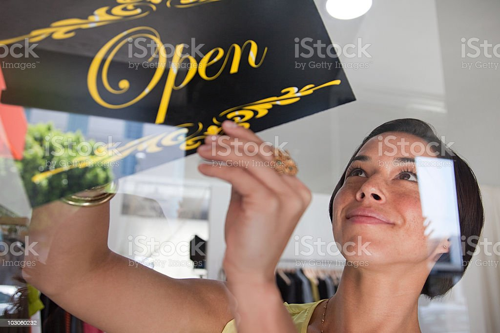 Shop assistant turning sign in shop window stock photo