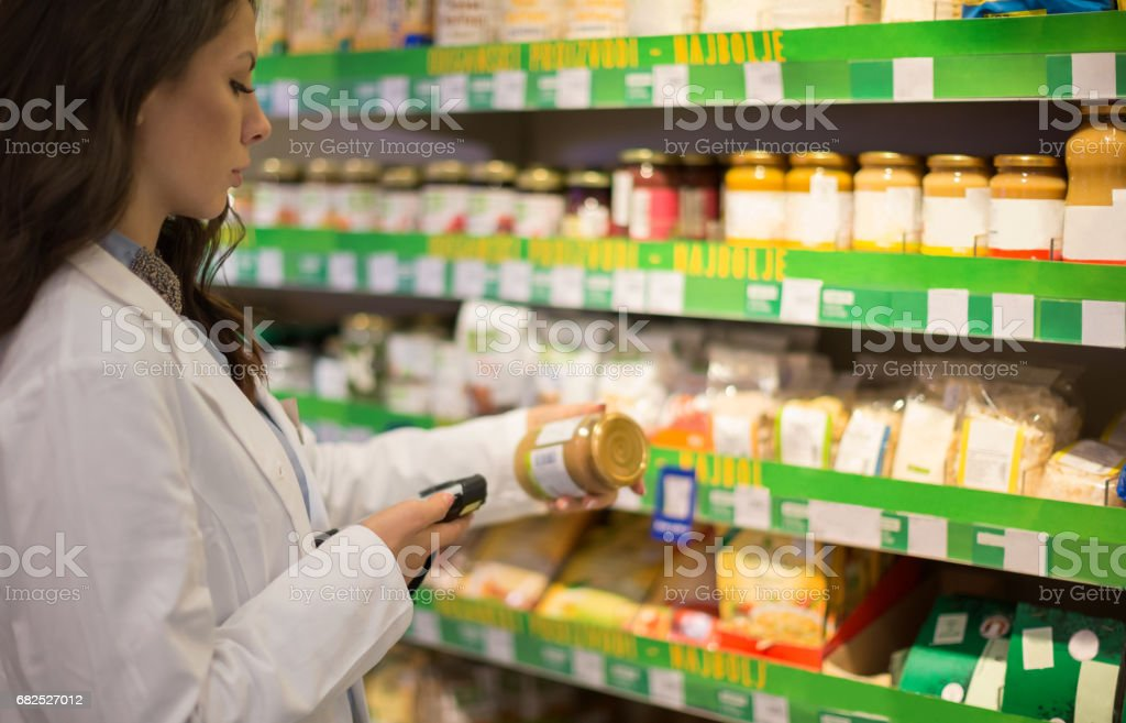 Shop assistant using bar code stock photo