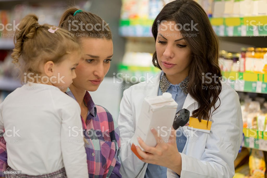 Shop assistant with mother and daughter stock photo