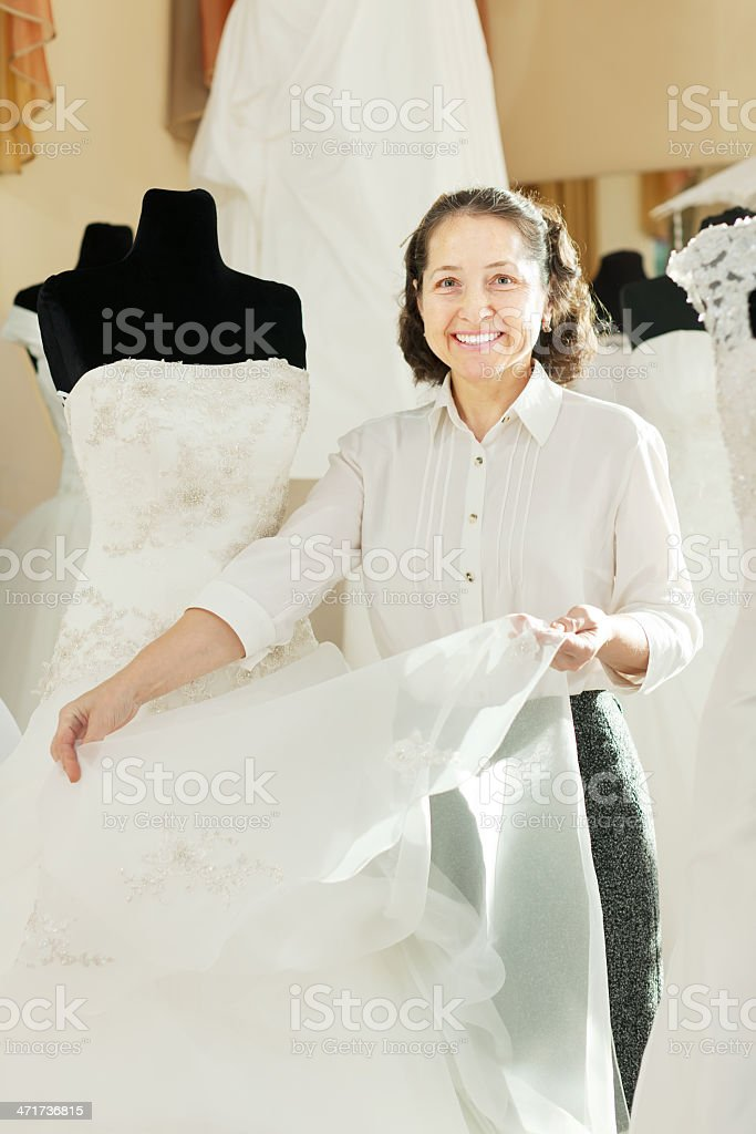 Shop consultant shows bridal dress royalty-free stock photo