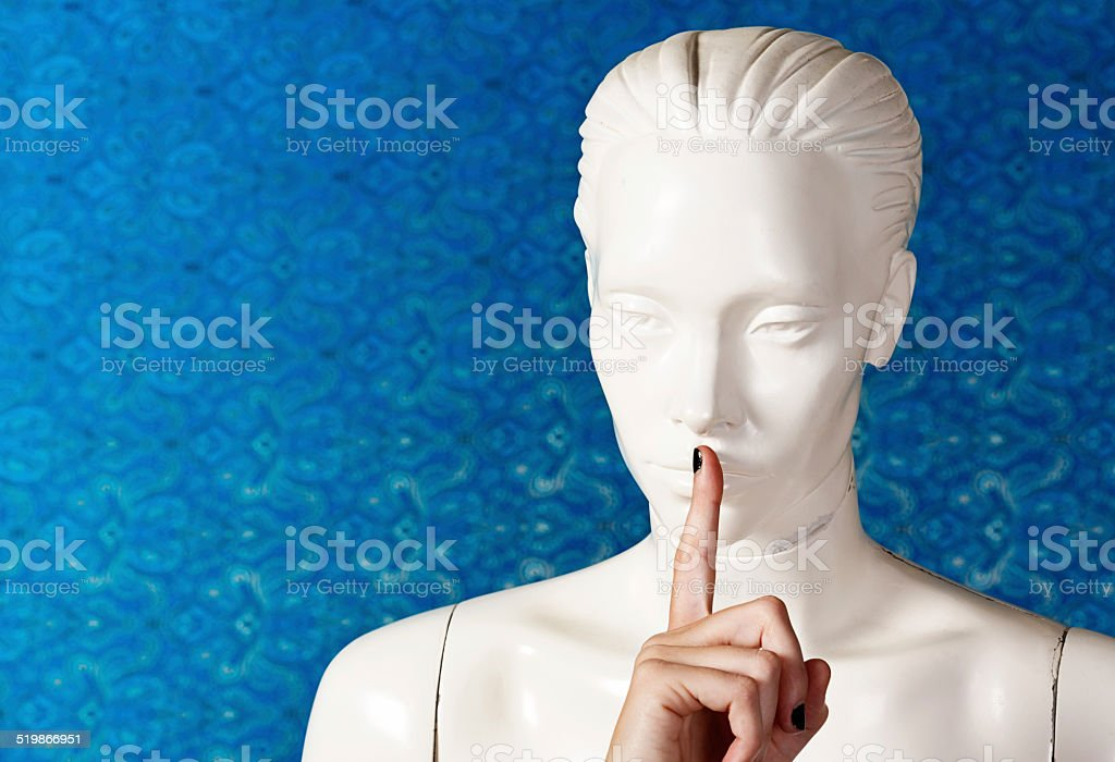 Shop mannequin, lips covered by human finger, keeps quiet! stock photo