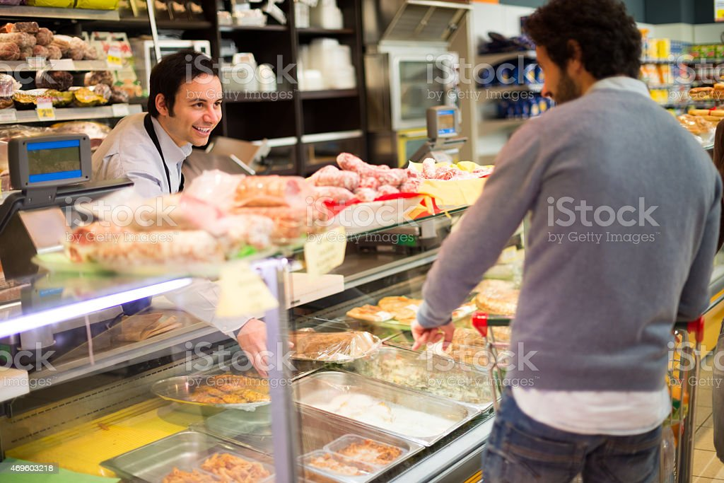 Shop owner serving a customer some food stock photo