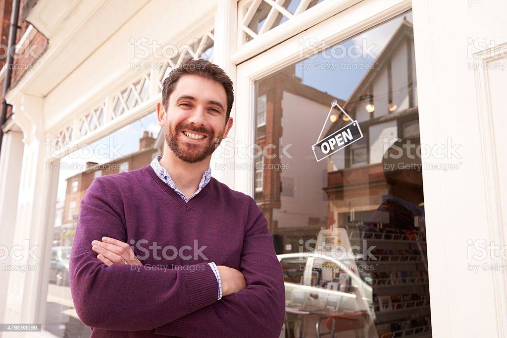 Shop owner standing next to his shop stock photo