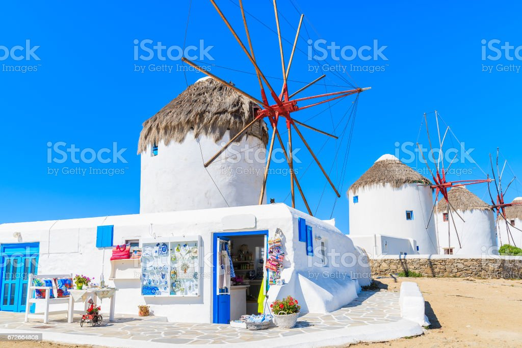 Shop with tourist souvenirs in front of famous traditional windmills on island of Mykonos, Cyclades, Greece stock photo