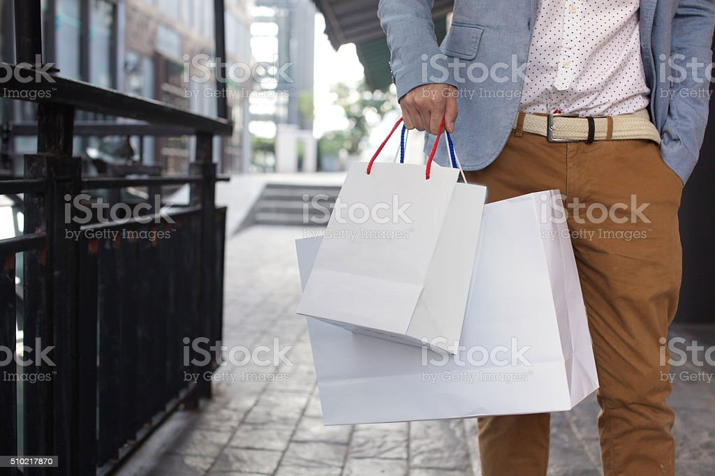 Shopaholic man walking on commercial street with shopping bags stock photo