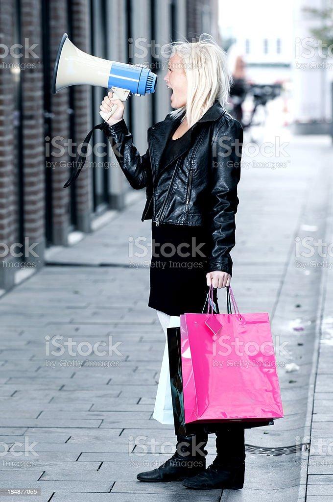 Shopaholic screams in a megaphone royalty-free stock photo