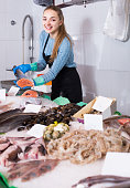 shopgirl with apron offering fresh fish in shop