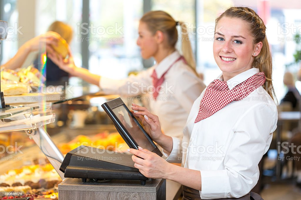 Shopkeeper at bakery working at cash register stock photo