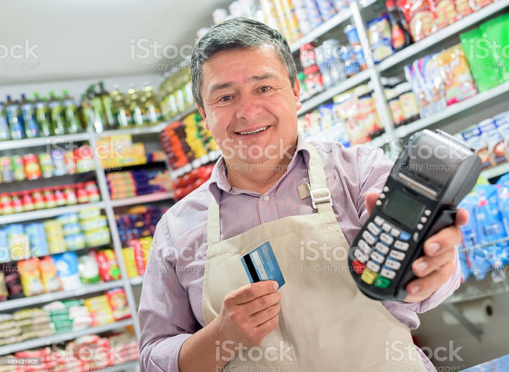 Shopkeeper holding a credit card machine stock photo