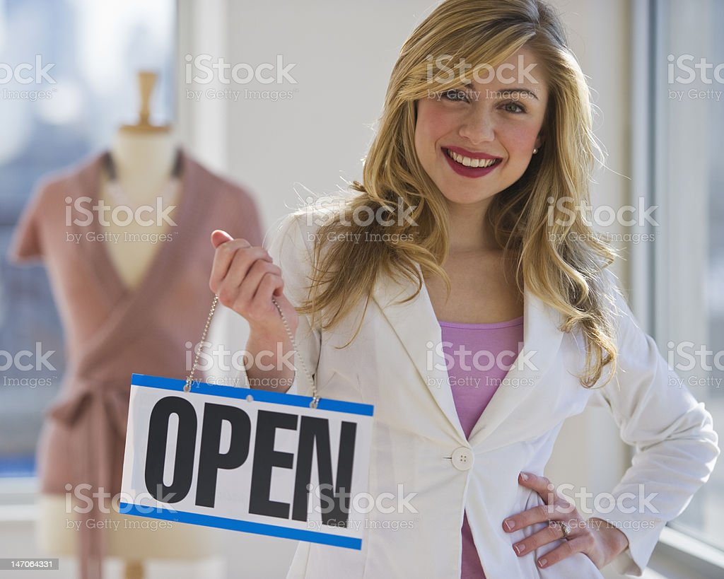 Shopkeeper holding blue open sign royalty-free stock photo