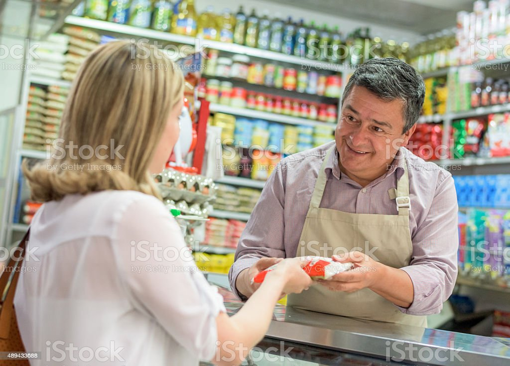 Shopkeeper selling food at his local shop stock photo