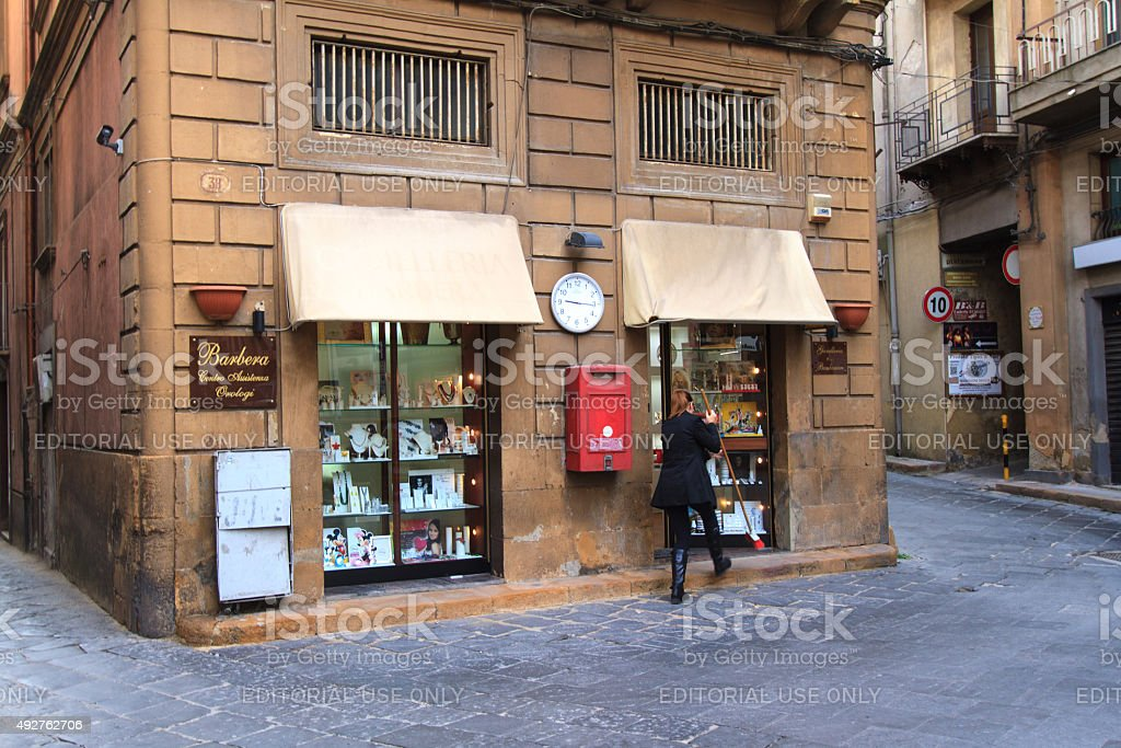Shopkeeper Sweeping Outside Shop in Piazza Armerina, Sicily stock photo