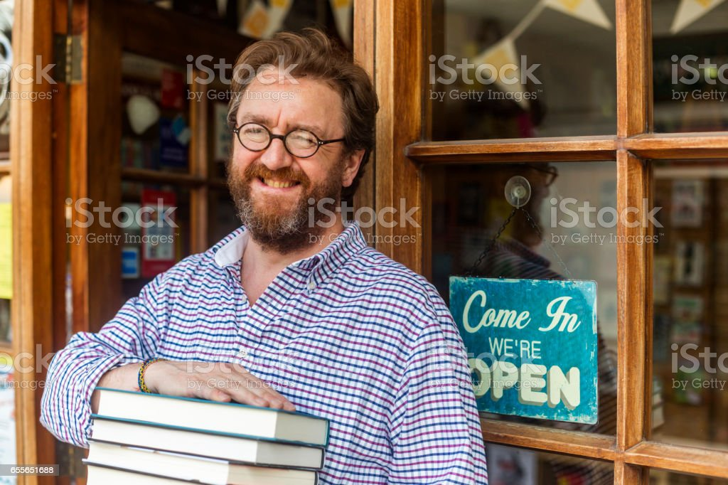 Shopkeeper Welcoming Customers to his Traditional English Bookshop stock photo