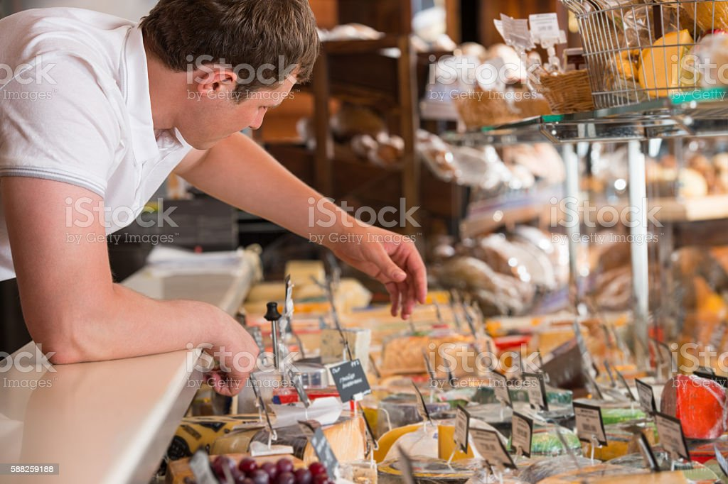 Shopkeeper working in a cheese glass case in grocery store stock photo
