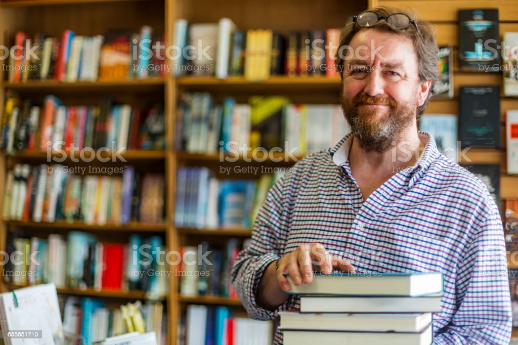 Shopkeeper Working in a Traditional English Bookshop stock photo