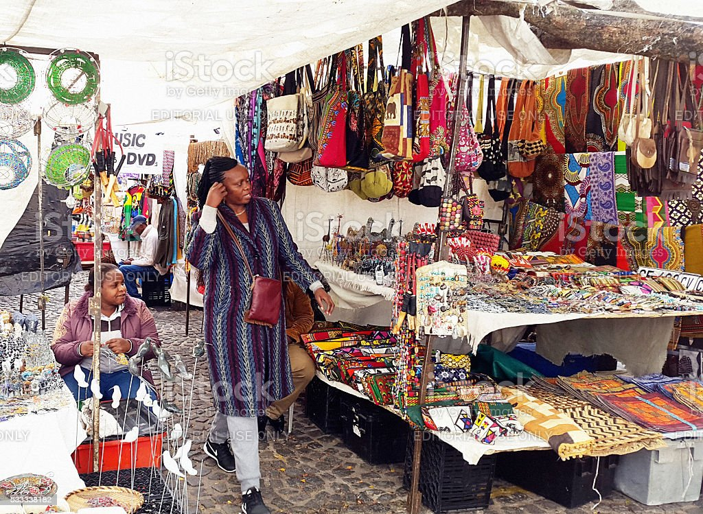 Shopper at Greenmarket Square, Cape Town, eyeing jewellery and curios stock photo