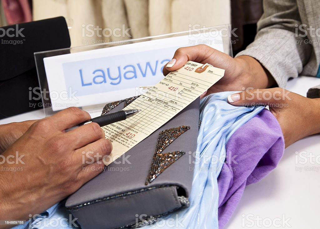 Shopper completing layaway tag at checkout counter. Retail store. Shopping. royalty-free stock photo