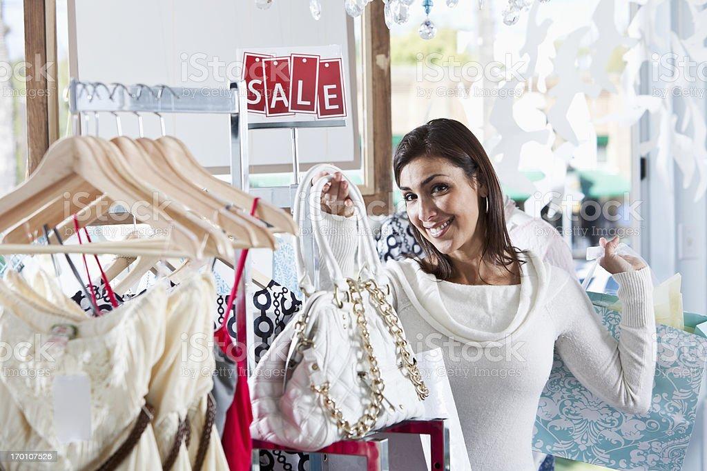 Shopper in boutique admiring handbag stock photo