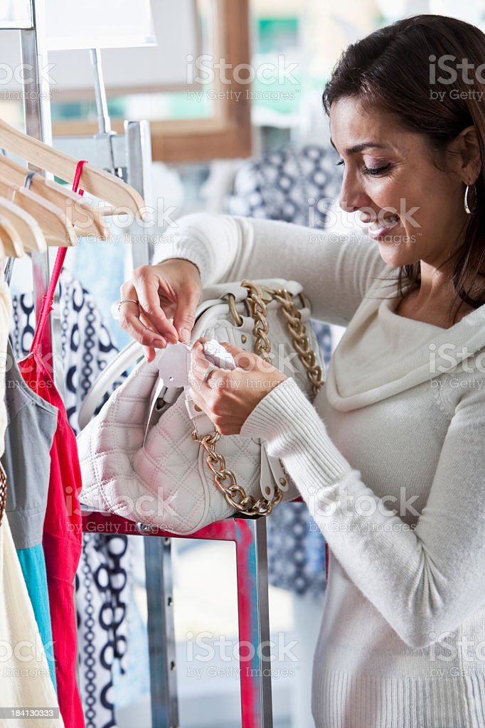 Shopper looking at price tag on handbag stock photo