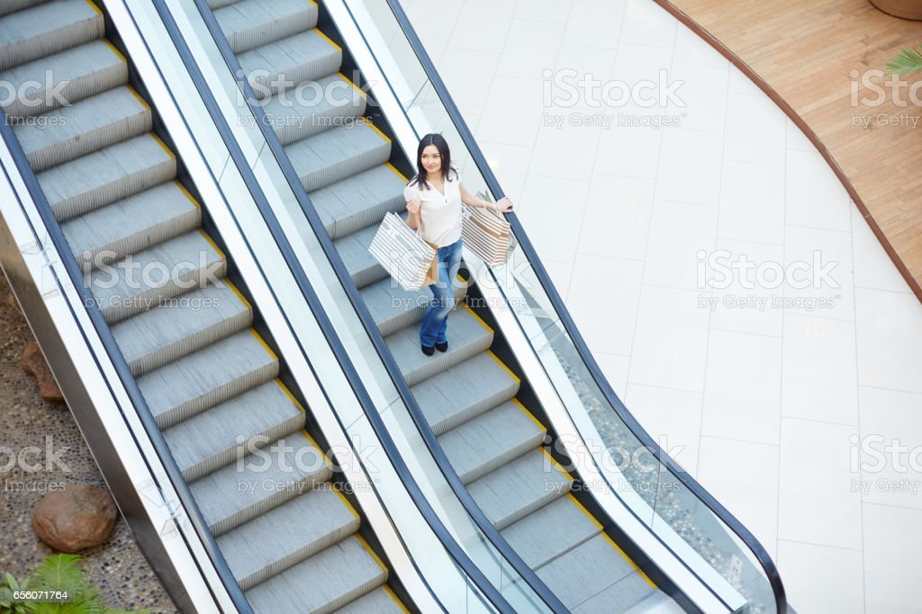 Shopper on escalator stock photo