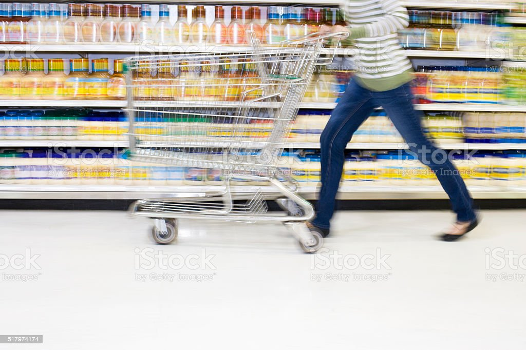 Shopper with in a hurry with cart in aisle stock photo
