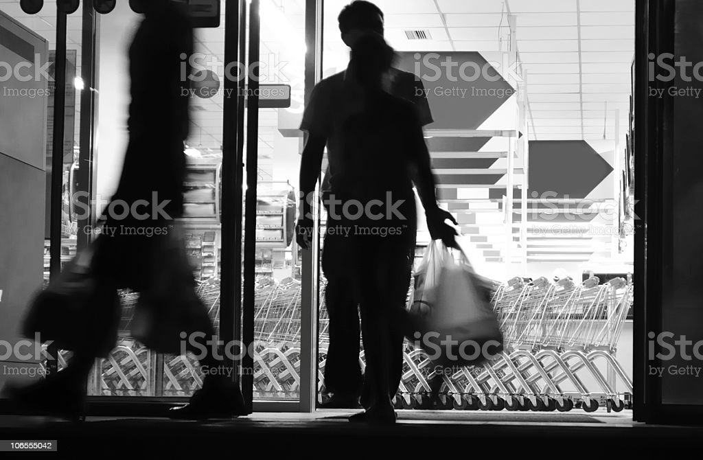 Shoppers exiting supermarket royalty-free stock photo