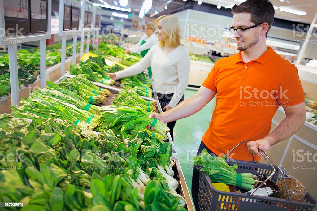 Shoppers in grocery store selecting vegetables stock photo