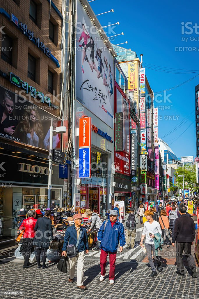 Shoppers on crowded street of stores colorful signs Seoul Korea stock photo