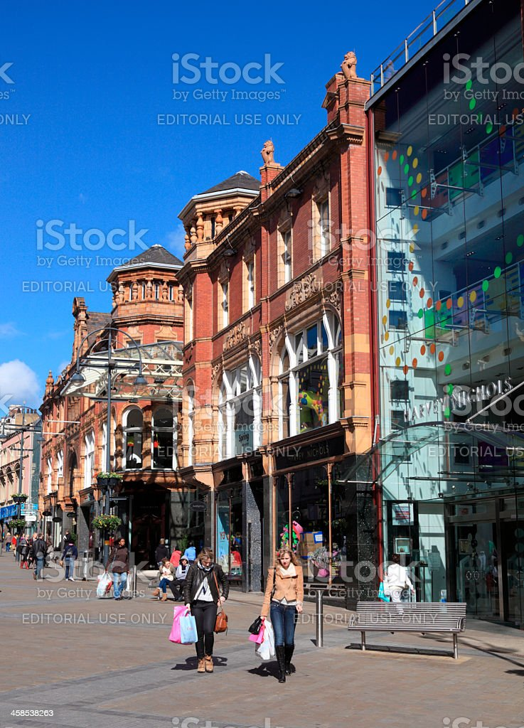 Shoppers walking past the Harvey Nichols store in Leeds royalty-free stock photo