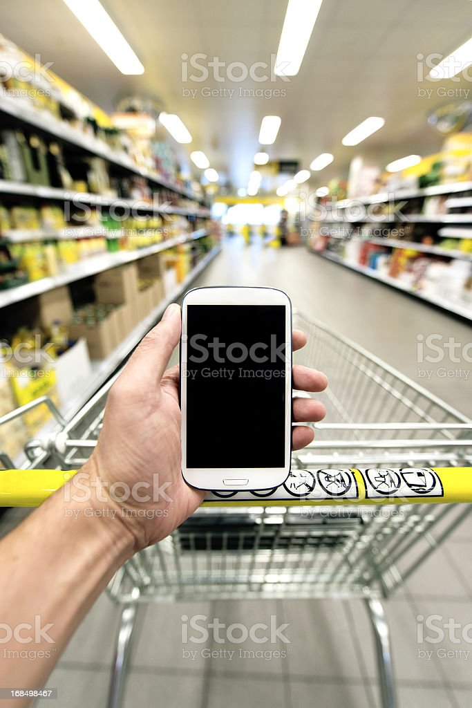 Shopping at the supermarked with smart phone stock photo