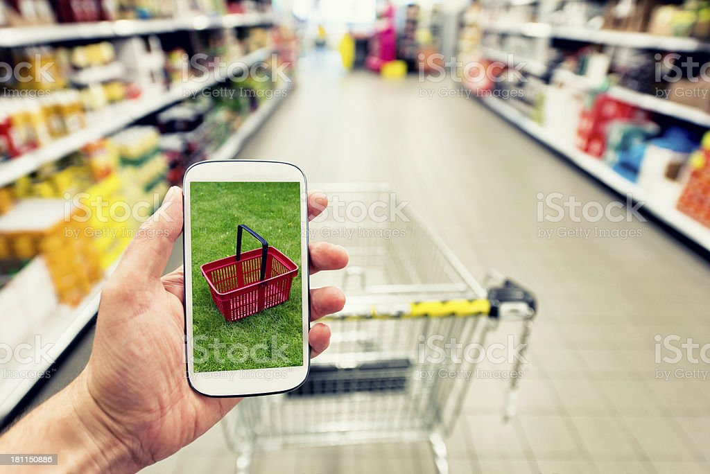 Shopping at the supermarked with smartphone royalty-free stock photo